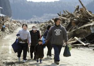 【共同】がれきが散乱した市街地を歩く被災した家族=2011年3月13日午前11時6分、宮城県南三陸町