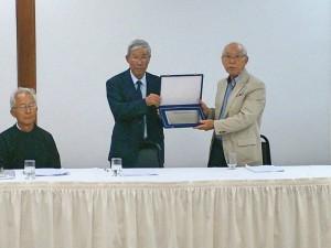 長年の貢献を称え青山新会長(左)から記念プラッカを受け取る山田前会長