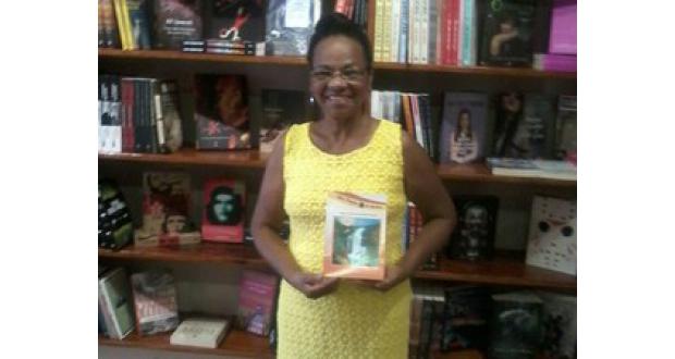 初の詩集を手に微笑むファッチマさん(Maria Lourdes da Silva/Divulgação)