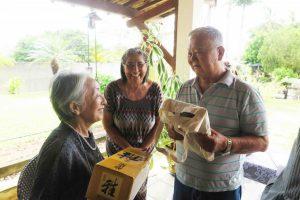 故郷巡り団長の玉城道子さん(青森県人会長)が松苗夫妻に記念品を贈呈