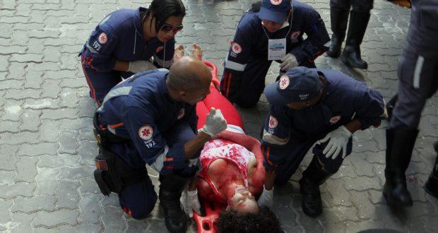 重傷者役のボランティアを運び出す救急隊員達(Carla Ornelas/GOVBA)