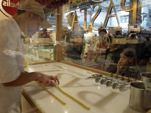 詰め物入りパスタ、ラヴィオリを作る職人の手作業を、へばりつくように見入る子供