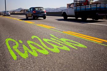 リオ2016の文字の横に緑の線が引かれた道路(Daniel Coelho/Seconserva)