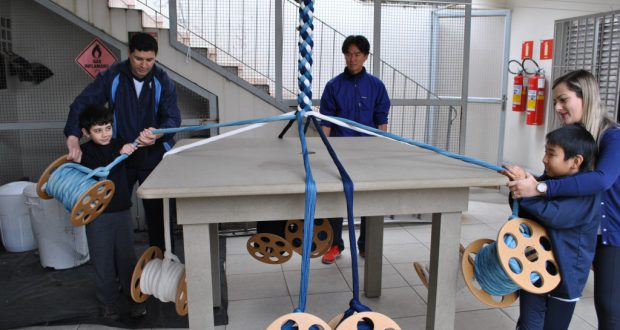 職員の手を借りながら編んでいく生徒らと、作業を見守る五十嵐さん(中央)