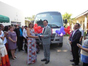 寄贈されたマイクロバスを前に記念撮影する関係者(提供写真)