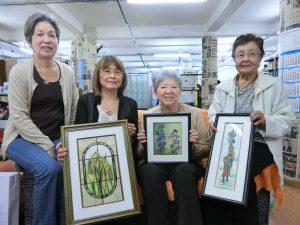 (左から)作品を手に展示会を心待ちにする関係者