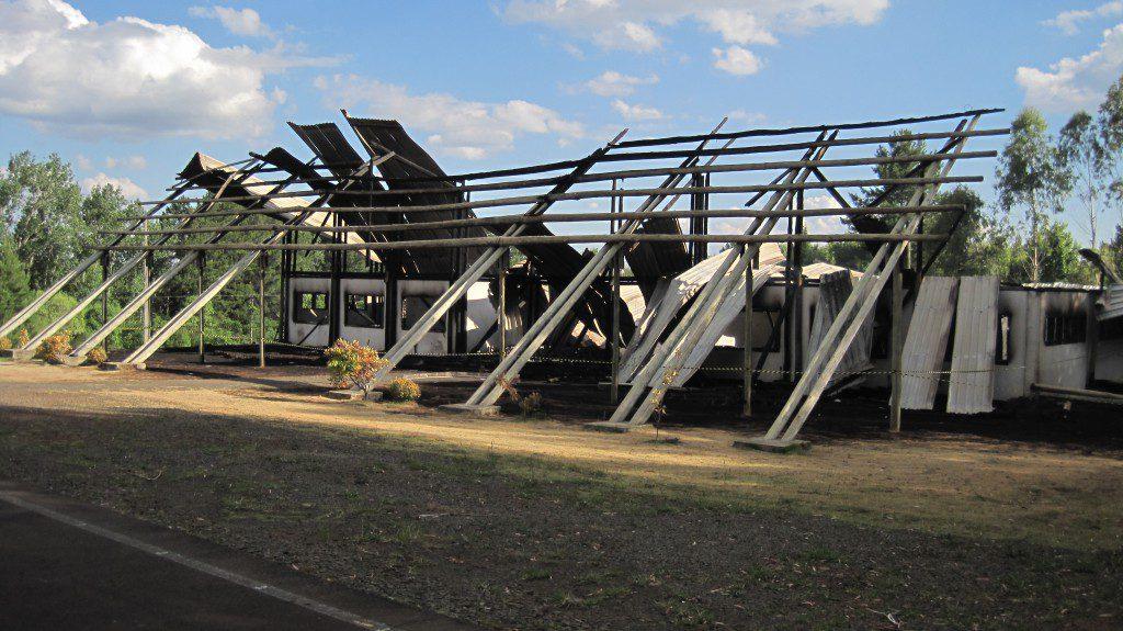 無残な姿になった平和資料館。事故から一夜明けた23日、ユーカリの支柱からはまだ煙が立っていたという(山本和憲さん撮影)