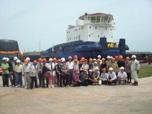 船台のプッシャーボートの前で一同記念写真