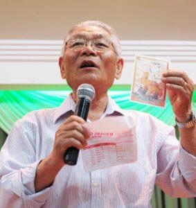 『トルデシリャス条約500周年記念式典』の記念切手を見せながら説明する会田清さん