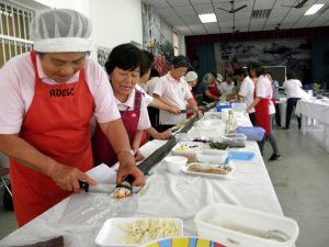「思いは一つの絆寿司」。巨大な巻き寿司を切り分ける婦人ら