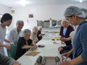 さくらホームで巻き寿司を作る食事イベントの様子(左端が村上さん)