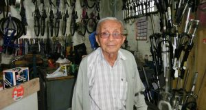 店頭で自転車店の手伝いをする日高さん