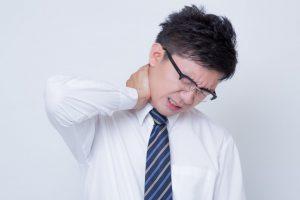 首の痛みを訴えるサラリーマン(写真素材ぱくたそ、www.pakutaso.com、photo すしぱく)