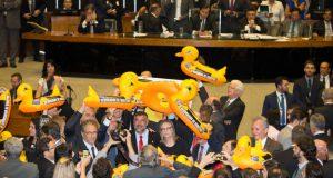 22日の下院採決の様子 野党議員は「つけ」を暗喩するアヒルの人形を掲げて抗議した。「失政のつけを労働者にまわすな」と主張している(Foto Lula Marques/AGPT)