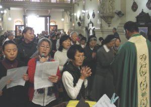 ミサで祈りを捧げる参列者