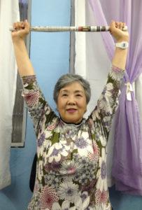 腕を上げる運動は体の老化防止に効果的と話す鈴木さん。補助的に棒状に丸めた新聞紙を使用