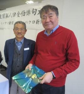 伊那宏選者(左)から特選の記念品を受け取る廣瀬芳山さん(右)