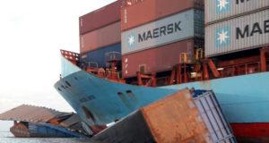 事故現場に滞留中の大型貨物船と舳先に張り付いた形のフェリーの一部(ASCOM CBMPA)