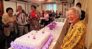「89」のロウソクがさされたケーキの前に、嬉しそうに立つ吉安園子さん