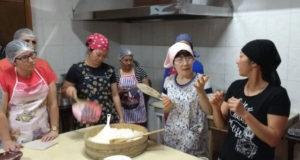 巻き寿司の作り方を指導する清水さん(右から2番目)