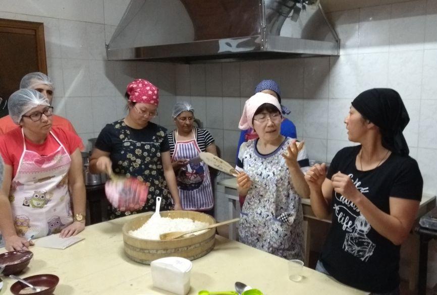 巻き寿司の作り方を指導する清水さん(左から2番目)