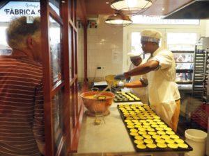 リスボンの旧市街アウグスタ通りにある有名店の軒先。コンロのすぐ横の熱い職場なせいか、名物お菓子「パステル・デ・ベレン」を作って見せるのはアフリカ系移民