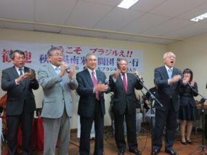 堀井副知事(右)ら南米訪問団全員が登壇し、歓迎会に参加した全員と秋田民謡「ドンパン節」を歌っている様子