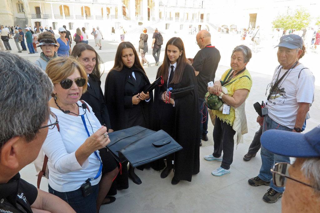 ガイドのミライさん(左)は、コインブラ大学の女学生をつかまえて、伝統的な衣装やカバンについて一行に説明