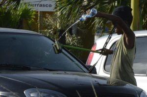 信号待ちの車に駆け寄り、「窓ガラスを拭くからお金を頂戴」とせがむ少年(参考画像・Valter Campanato/Agência Brasil)