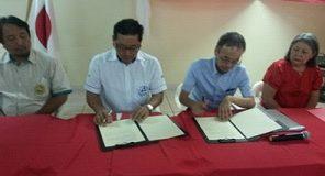 (左から)署名する乙幡会長、濱田事務所長