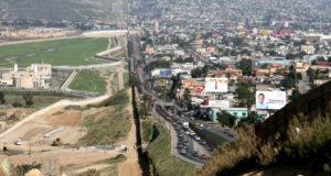 ラ米諸国と米国を隔絶する「呪いの壁」。左側がサンディエゴの国境警備隊事務所、右側がメキシコティフアナの間の国境フェンス(By Sgt. 1st Class Gordon Hyde [Public domain], via Wikimedia Commons)