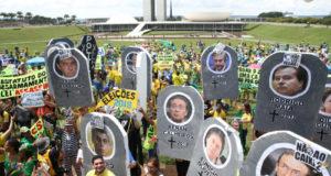 政治家や企業家の顔写真を掲げて、汚職反対デモを行う人々(Antonio Cruz/Agência Brasil)