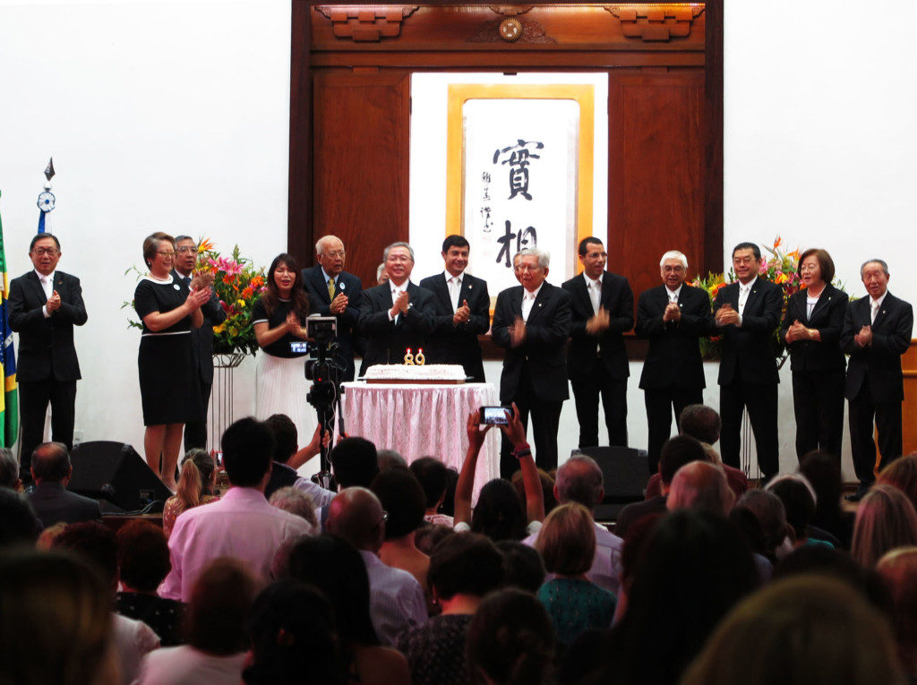 ケーキを前に「使命行進曲」を大合唱する幹部や来賓