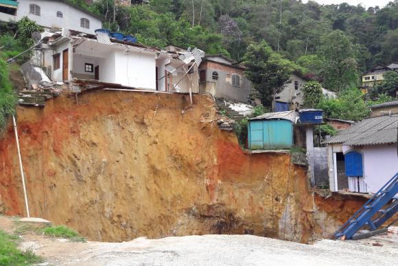 大雨で増水した川と、土砂が流され、崩壊の危険にさらされている家々(Divulgação/Prefeitura de Petrópolis)