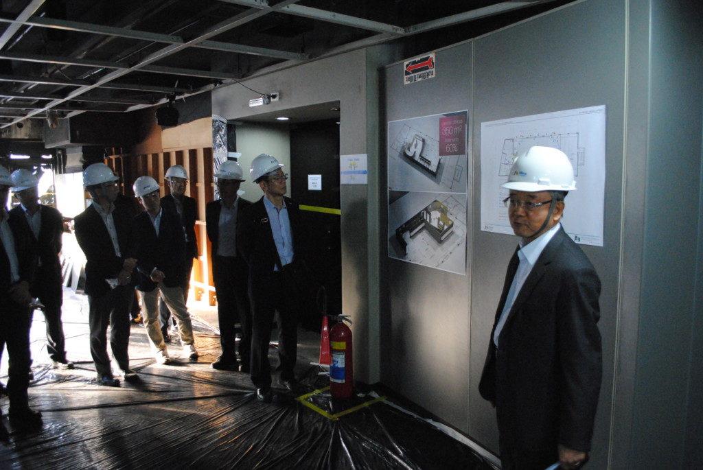 工事中の8階で改修計画の説明を聞く参加者たち