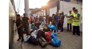 バスに分乗して聖市のCTAに到着したベネズエラ人とそれを迎える職員達(Rovena Rosa/Agência Brasil)