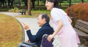 屋外の車椅子の男性と介護士(日本、フリー写真サイト「写真AC」より)