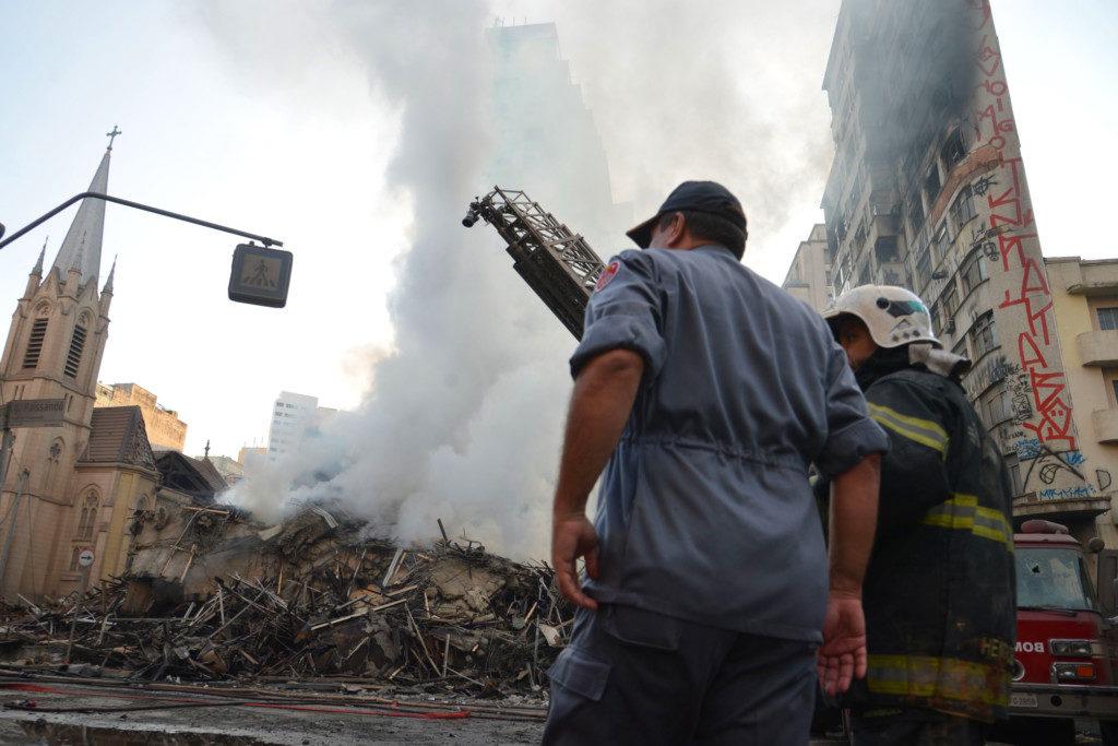 昼になっても延焼が続く崩落現場で消火作業をする消防士たち(Foto Rovena Rosa/Agencia Brasil)