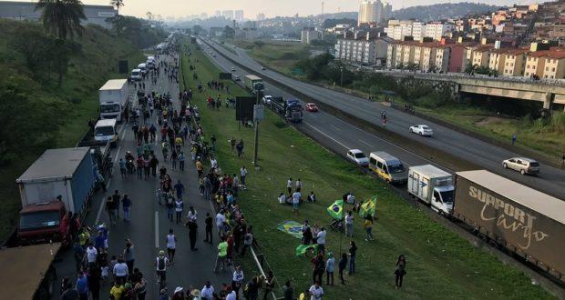 幹線道路脇に停められたトラックと路上に広がった運転手達(Roberto Parizotti)