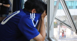 試合終了後、泣き顔を隠して窓際にたたずむ男性