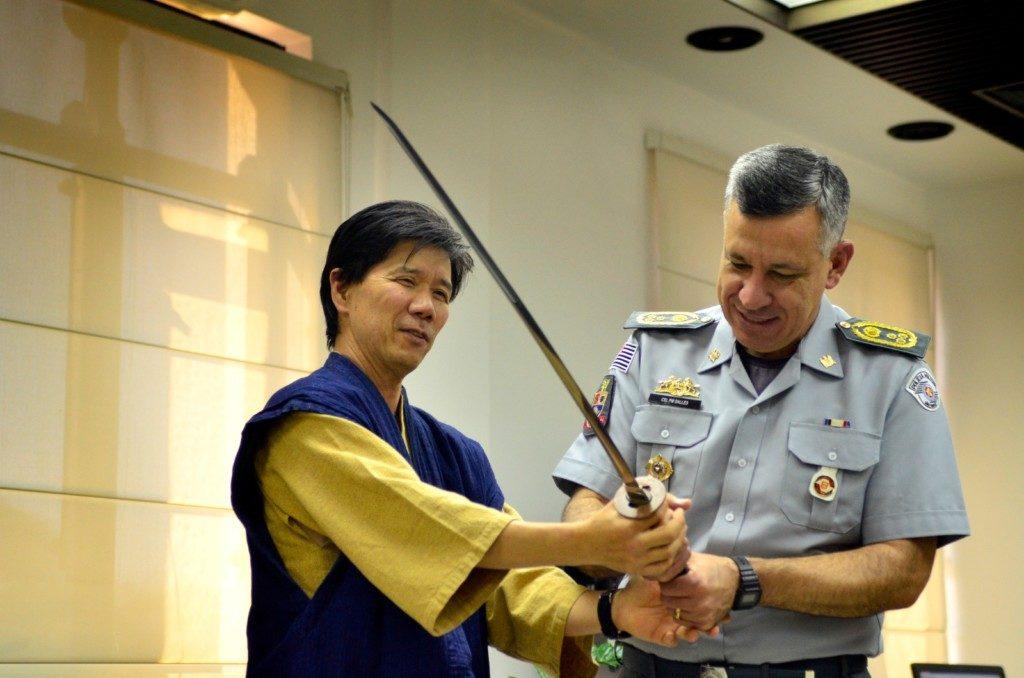 マルセロ・ヴィエイラ・サーレス大佐に日本刀を見せる岸川さん(提供写真)