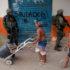 ライフルを持った兵士の横を半裸の子供が平気で歩いている。(Fernando Frazao / Agencia Brasil)