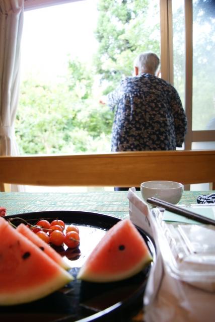 暑い夏、スイカを食べて涼をとる高齢者(参考写真)