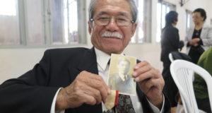 戦死した父の遺影と勲章を手に微笑む谷口さん