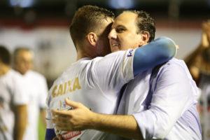 昇格を決め、選手と抱き合う、フォルタレーザのロジェリオ・セニ監督(右)(Lucas Figueiredo/CBF)