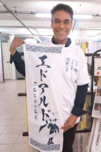 特製Tシャツを着て、手ぬぐいを持つエドアルド。「ぜひ応援してください」と笑顔で呼びかけた