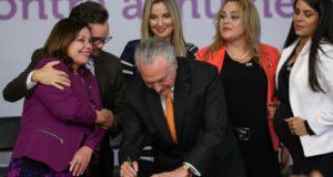 マルセラ夫人や女性議員らに囲まれ、家庭内暴力廃絶計画にサインする大統領(Marcos Corrêa/PR)