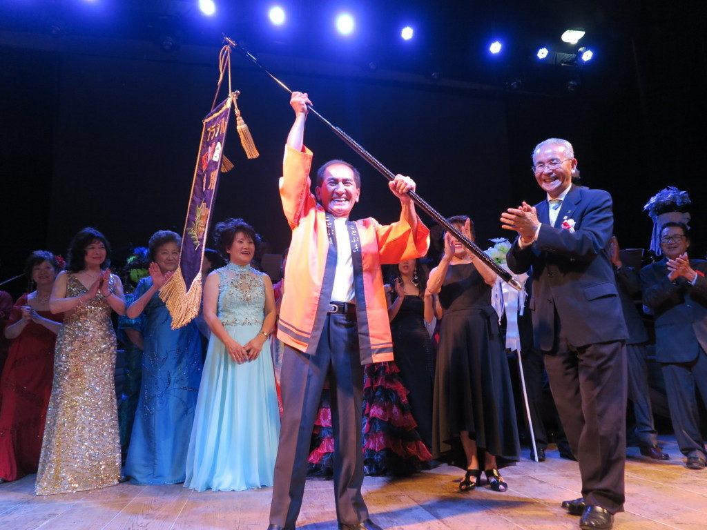 菊地実行委員長から手渡されたNHK寄贈の優勝旗を高々と掲げる高畑さん