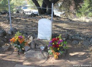 アメリカ本土で最初に亡くなった日本人女性おけいの墓。墓参りに来た人が手向けた花や、おけいの故郷会津の郷土玩具「赤べこ」もお供えされていた(写真=吉田純子)