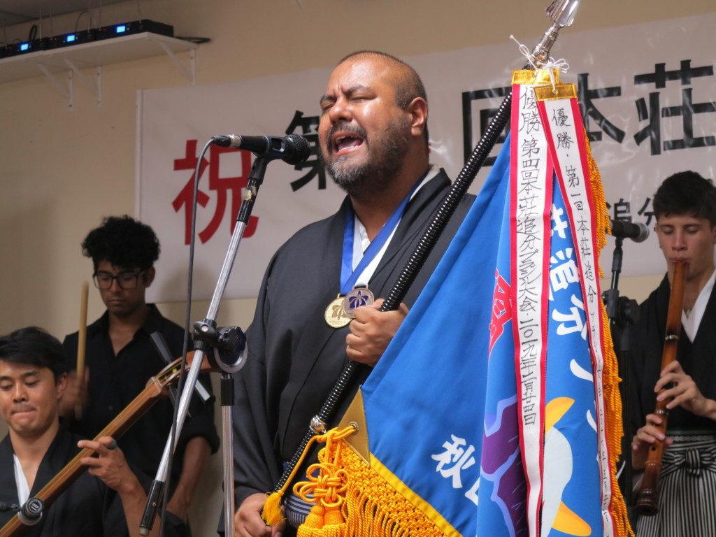 優勝旗を手に歌う高木さん